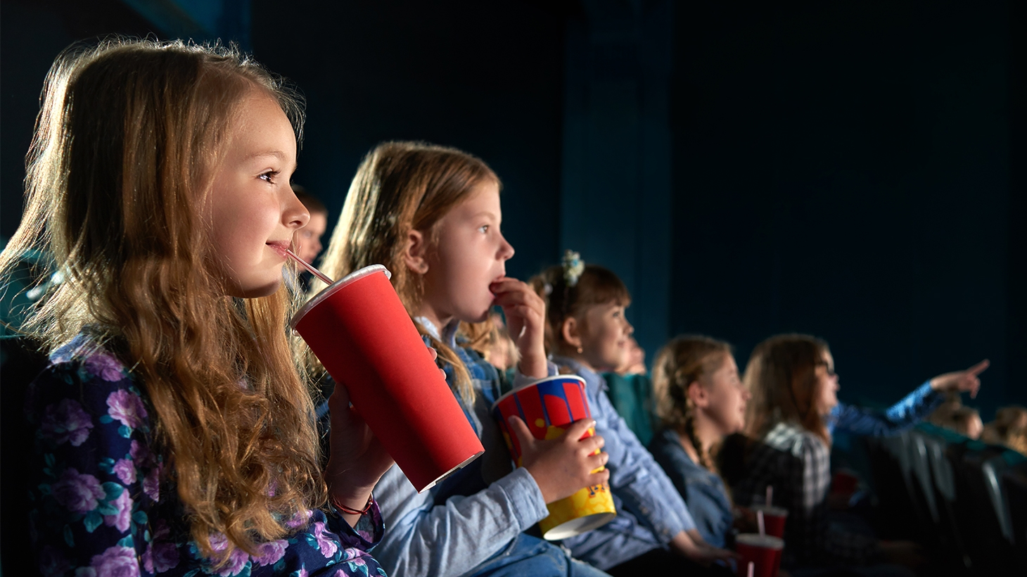 Group of kids watching a movie while eating popcorn and drinking soda