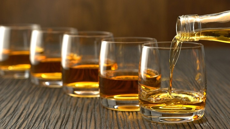 Glasses of whisky lined up on a table