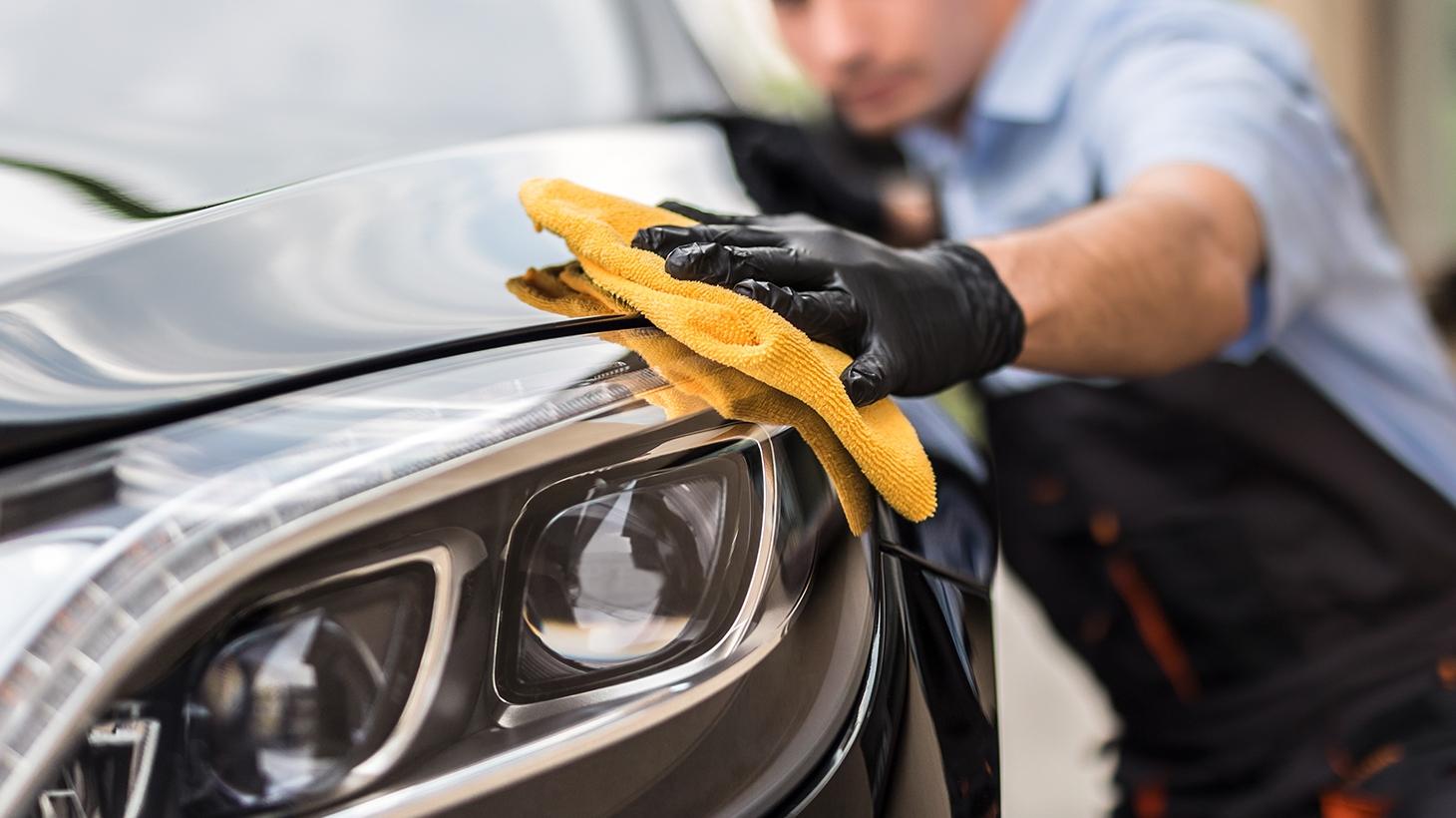 Closeup of man polishing a car