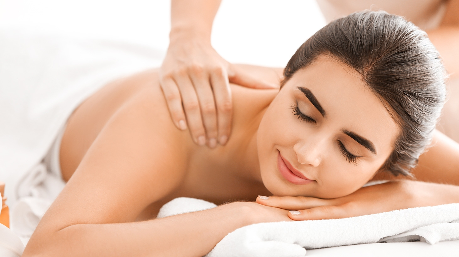 Woman laying on massage bed receiving back massage