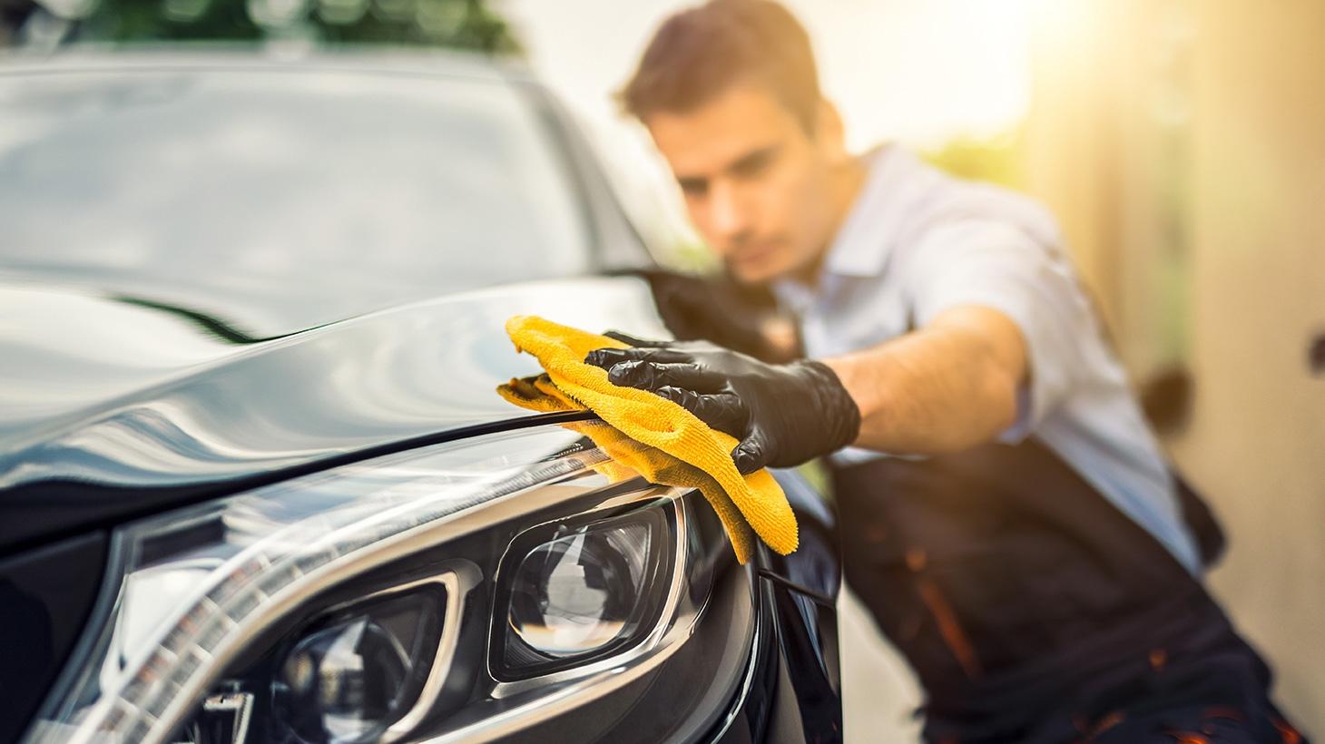 Man hand drying car at car wash