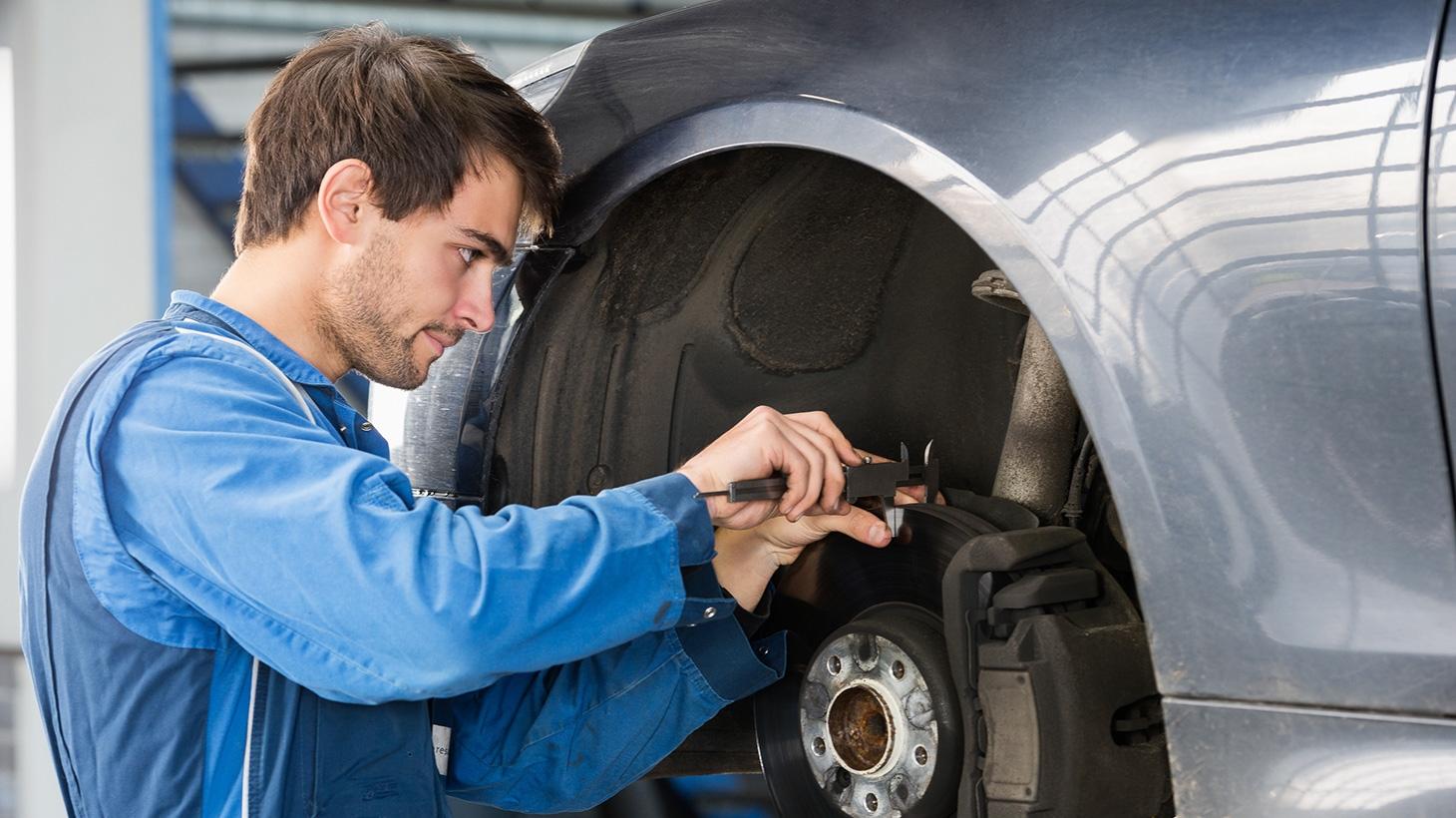 Mechanic checking brakes on car in work shop
